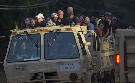 In this Sunday, Aug. 14, 2016 photo, Louisiana Army National Guard dump truck, loaded with rescued flood victims, makes it way back to dry land in Walker, La., after heavy rains inundating the region,(AP Photo/Max Becherer)